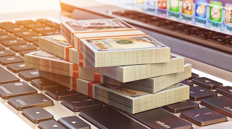 Ganar dinero en línea: pila de efectivo en la computadora portátil