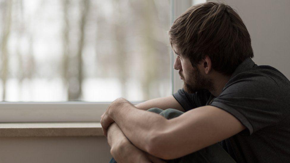 Trabajando remotamente solitario hombre sentado junto a la ventana