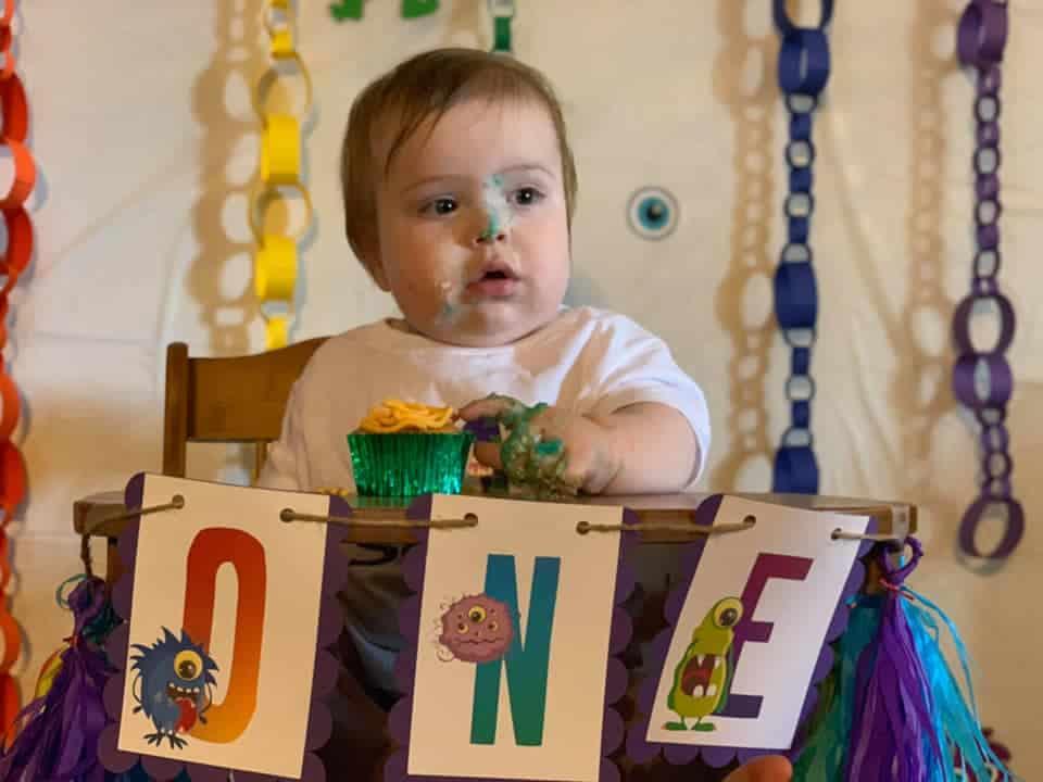 Mi hijo Sam disfruta de un pastelito en su trona. Como puede ver, hicimos un tema de monstruo arcoíris.