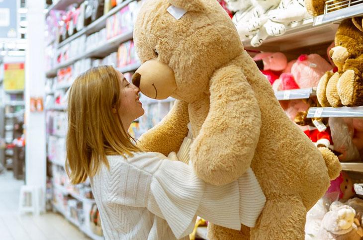 mujer comprando un oso de peluche