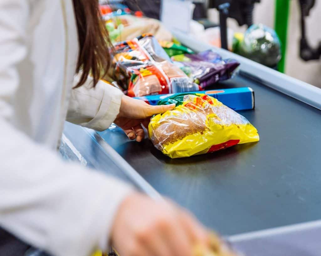 Colocación de alimentos en la cinta transportadora de la tienda de comestibles