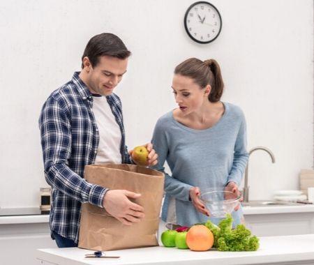Hombre mostrando contenido de bolsa de supermercado a esposa
