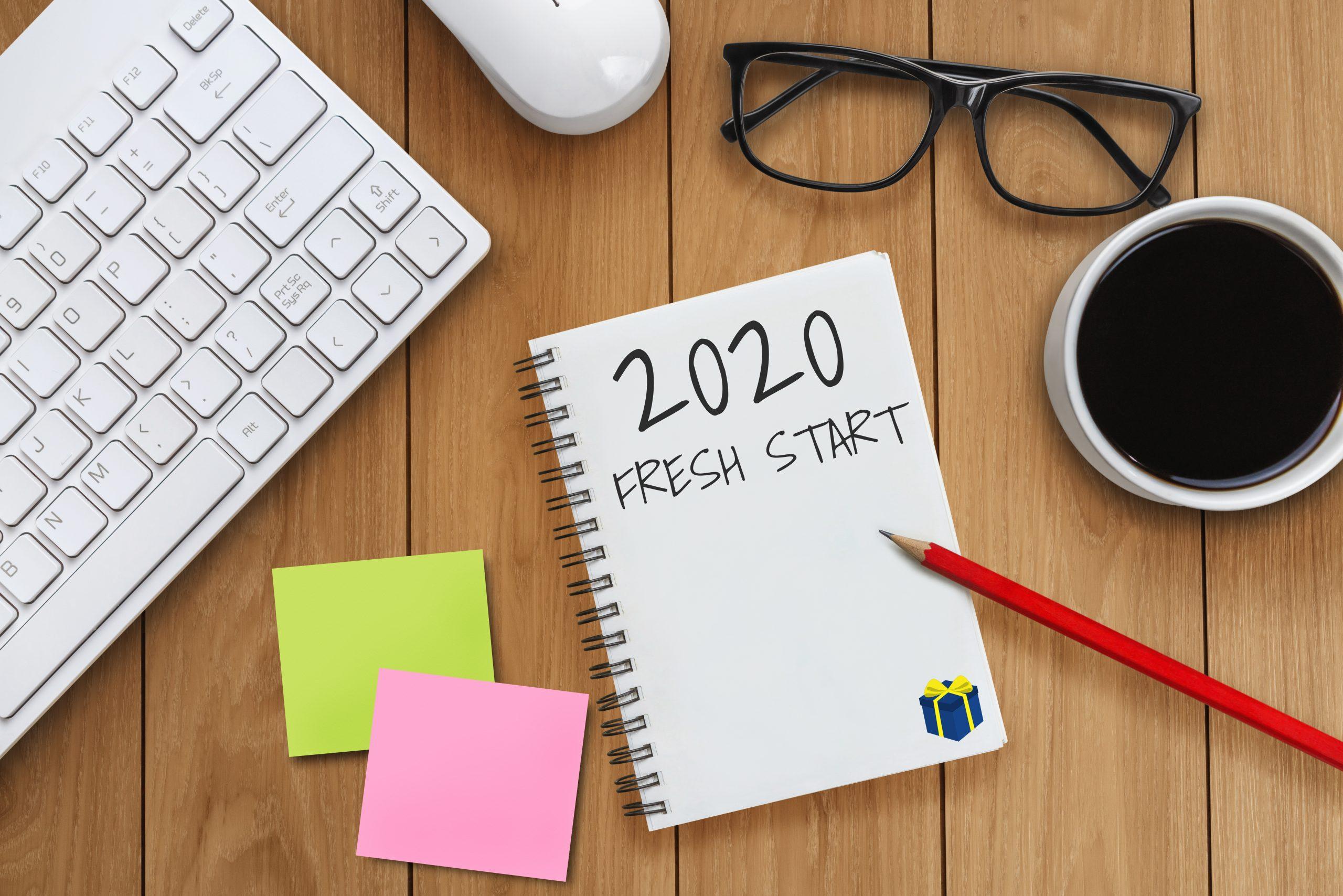 Obteniendo SMART en 2020. Establecimiento de objetivos para aquellos que desean resultados reales. Un cuaderno, un lápiz y una taza de café se sientan en un escritorio.