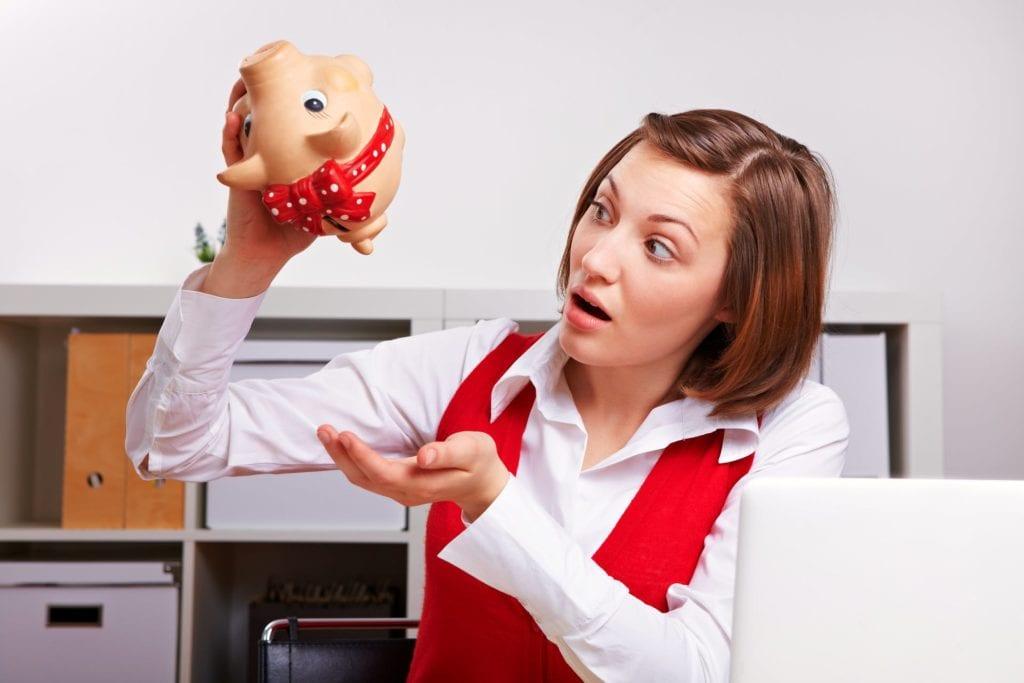 A woman empties a piggy bank