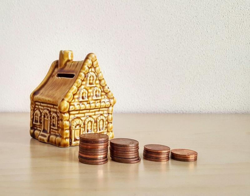 Monedas frente a una casa modelo.