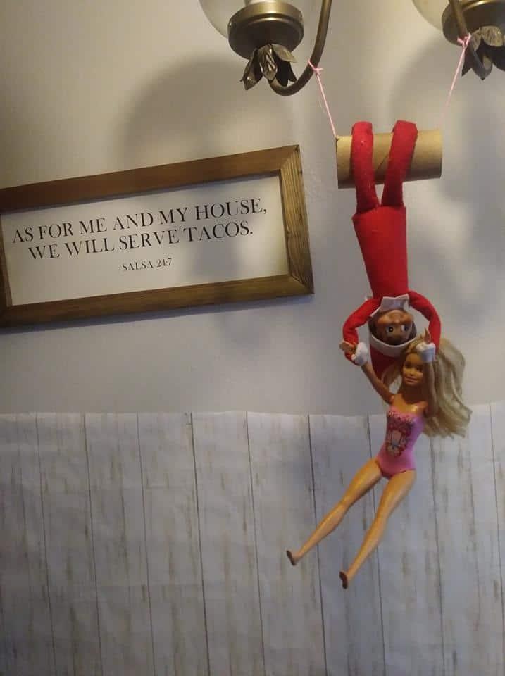 Un momento acrobático con Barbie, colgando de la lámpara de la cocina. Por favor, ignore mi pared extraña, uso la parte inferior para un fondo fotográfico para mis manualidades.