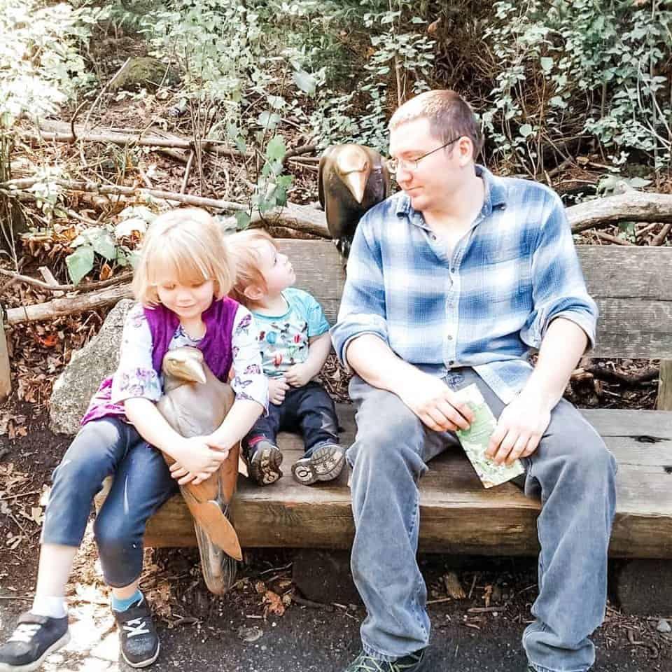 niños y esposo en el zoológico por estatuas de cuervo